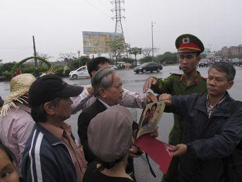 Công an giật bích chương ra khỏi tay người biểu tình trước tòa án. Hình: AP