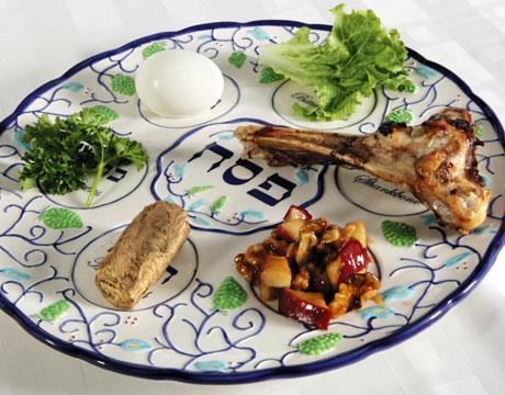 Một dĩa seder với rau parsley, trứng luộc, rau romaine lettuce, xương cừu nướng, táo và hạt trộn rượu, và khoai.