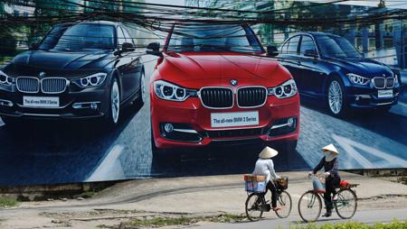Người, bảng quáng cáo (Hà Nội). Nguồn: AFP