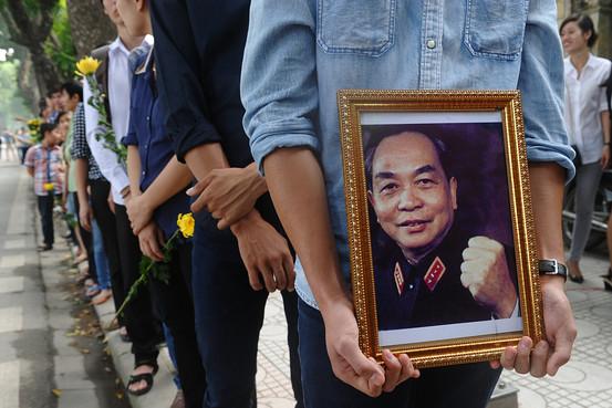 Một người đàn ông nắm giữ một bức chân dung của cuối Đại tướng Võ Nguyên Giáp khi ông lên đường trong số hàng ngàn người khác bên ngoài nơi cư trú của cuối Đại tướng Võ Nguyên Giáp trước khi đi để tỏ lòng tôn kính người anh hùng độc lập dân tộc tại Hà Nội ngày 06 tháng 10 năm 2013. Nguồn: Agence  France-Presse/Getty