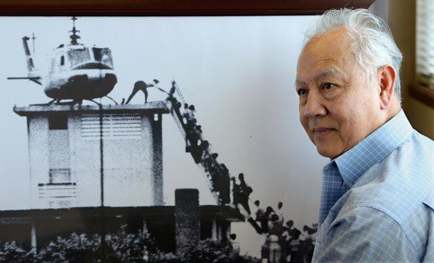 Dr. Huynh Tong trước bức ảnh của Hubert van Es chụp nhóm người lên trục thăng rời Saigon ngày 29/4/1975 từ nóc cao ốc số 22 đường Gia Long. Ông là người thứ 2 trên thang. Nguồn: VINO WONG / VWONG@AJC.COM