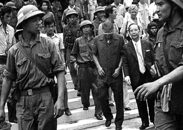 30 April 1975: Tướng Dương Văn Minh (G, cúi mặt), tổng thống sau cùng của VNCH, bên cạnh cựu nghị sĩ Vũ Văn Mẫu – Thủ tướng nội các DVM - và đoàn tùy tùng rời Dinh Độc Lập ngày 30 tháng 4 1975 sang đài phát thanh đọc lời tuyên bố  đầu hàng sau khi bị Cộng quân Bắc Việt bắt. Tiền cảnh là sĩ quan CSBV Phạm Xuân Thệ (P) và Bàng Nguyên Thất (T). Nguồn ảnh: AFP/Getty Images