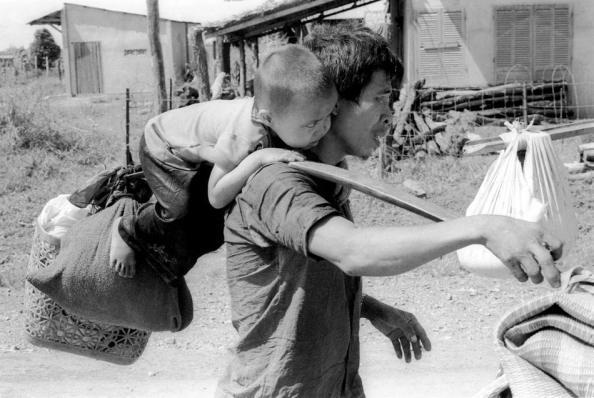 Một người cha miền Nam Việt Nam gánh con và túi vật dụng gia đình rời khỏi ngôi làng của mình gần Trảng Bom trên Quốc Lộ 1 phía tây bắc của Sài Gòn ngày 23 tháng 4 1975. Nguồn ảnh: AP Photo / KY Mhan.