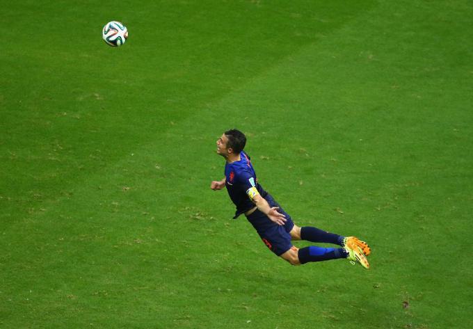 Robin van Persie ghi bàn thắng cho Netherlands bằng cú bay đội đầu trong hiệp đầu của trận đấu với Spain tại FIFA World Cup Brazil 2014, Nhóm B tại cầu trường Fonte Nova hôm 13 tháng Sáu, 2014 tại Salvador, Brazil. Nguồn : Jeff Gross / Getty Images.