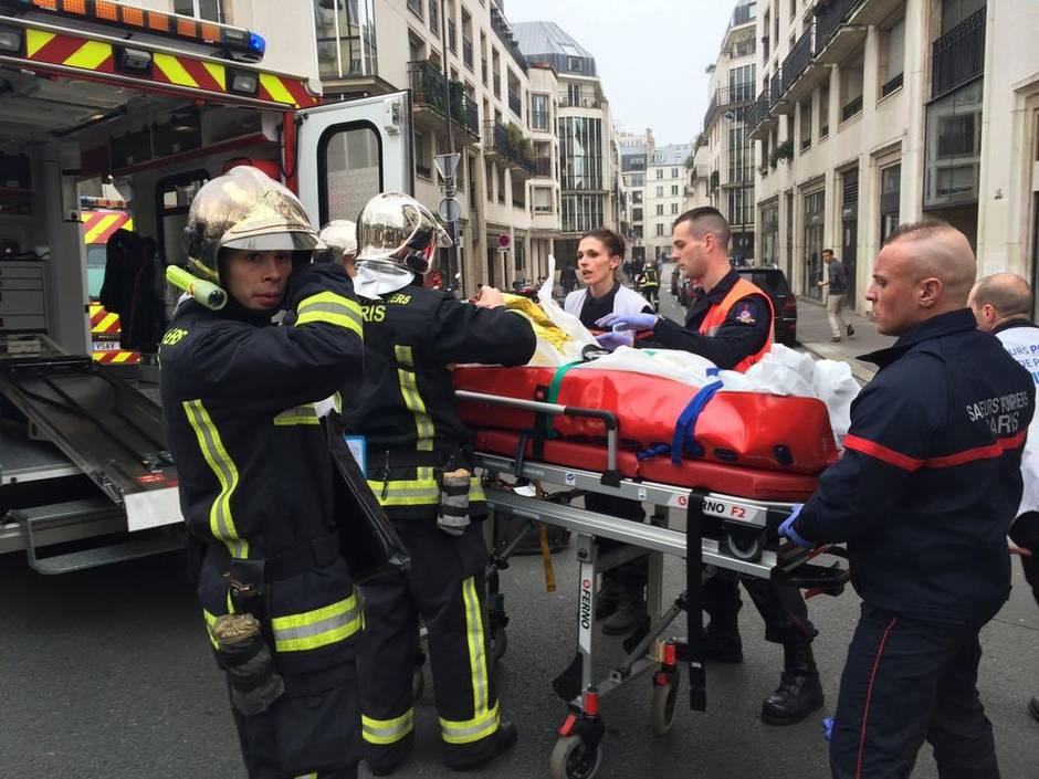 Nhân viên cứu hỏa mang theo một người đàn ông bị thương trên cáng ở phía trước của văn phòng Charlie Hebdo. (Philippe Dupeyrat / AFP / Getty Images)