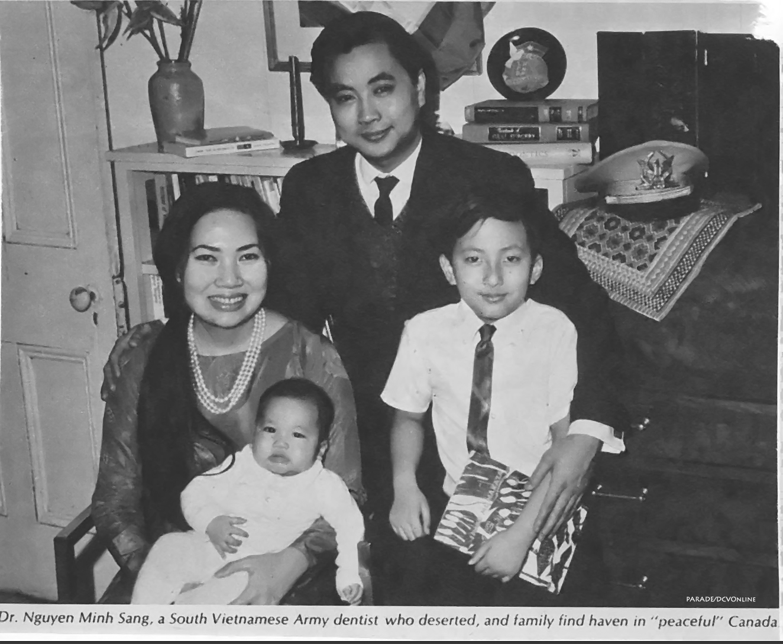 Cựu đại úy quân nha đào ngũ Lê Minh Sang bên vợ con, mũ sĩ quan VNCH và sau lưng là cờ MTGPMN.