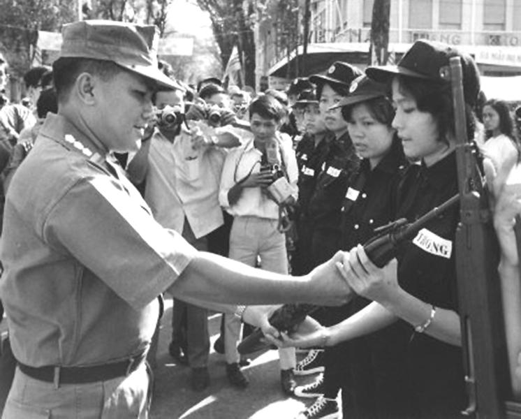 Đô trưởng Saigon-Gia Định, Đại tá Đỗ Kiến Nhiễu trao vũ khí cho nữ đội viên Nhân dân tự vệ. Tháng 8/1969. Nguồn flickr.com