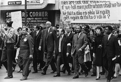 """""""Dẫn đầu đoàn diễu hành chống lại các cuộc xung đột Việt Nam có tiến sĩ Benjamin Spock, cao lớn, người đàn ông tóc bạc trắng, và Tiến sĩ Martin Luther King Jr., thứ ba từ bên phải, trong một cuộc diễu hành trên bang St. ở Chicago, Ill., March 25, 1967. Tiến sĩ Spock là đồng chủ tịch của Ủy ban Quốc gia về chính sách hạt nhân Sane. """"(AP Photo)"""