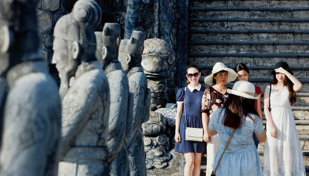 Khách du lịch chụp ảnh bên lăng vua Khải Định, phía nam Huế. Khải Định, Hoàng đế thứ mười hai của triều Nguyễn, đã được người Pháp đưa lên ngôi vào năm 1916. Bên trái là các bức tượng quan chức triều Nguyễn. © Maika Elan