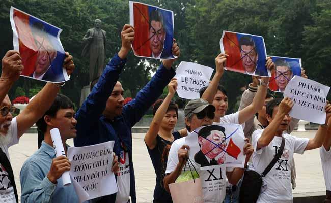 Những người biểu tình hô to các khẩu hiệu chống Trung Quốc cùng lúc cầm hình của Tập Cận Bình bih vách tréo trên trán tại công viên Lenin ở phía trước toà đại sứ Trung Quốc ở trung tâm thành phố Hà Nội ngày 05 tháng 11 năm 2015. Nguồn: ndtv.com