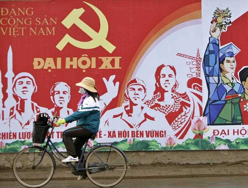 Một cô gái đi xe đạp qua một tấm bích chương quảng bá cho Đại hội toàn quốc lần thứ 11 của Đảng Cộng sản Việt Nam vào tháng Giêng năm 2011. Đại hội Đảng lần thứ 12 sắp tới, sẽ được tổ chức vào đầu năm 2016, sẽ xác định tư thế kinh tế và an ninh mới của Việt Nam. Nguồn ảnh: AAP
