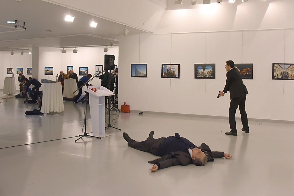Một người đàn ông, bên phải, theo tin của AP là sát thủ, sau bắn chết đại sứ Nga, nằm trên sàn, vào thứ Hai – 19 tháng 12 – tại một phòng triển lãm ở Ankara, thủ đô của Thổ Nhĩ Kỳ. Nguồn: Yavuz Alatan / Agence France-Presse - Getty Images